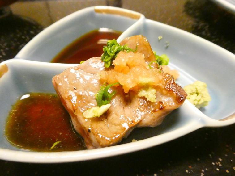 熱海_さくらや旅館_夕食 ステーキをタレをつけて食べる